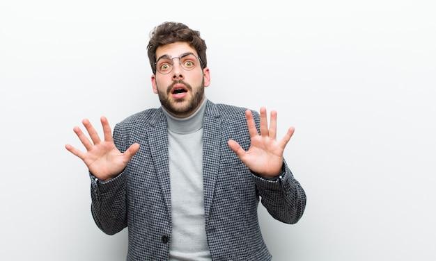 Junger managermann, der verblüfft und erschrocken sich fühlt und etwas fürchtet, das, mit den händen erschreckt, die offen sind, die vorderes sprichwort sagen, bleiben weg