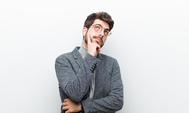 Junger managermann mit einem starken blick, wundernd mit einem zweifelhaften ausdruck und schauen oben und zur seite gegen weiße wand