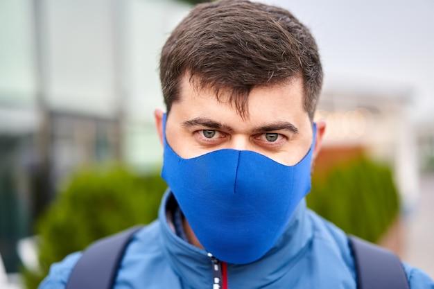 Junger mann 30 jahre alt in gesichtsmaske als schutz vor pandemie der coronavirus-covid-19-infektion im freien.