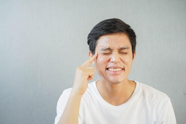 Junger mann (30 jahre), der mit dem finger auf das gesicht zeigt, um falten um die augen zu zeigen