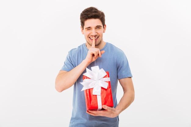 Junger mann 30s, der geschenkbox mit bogen hält und mit finger auf lippen geheim hält, lokalisiert über weißer wand