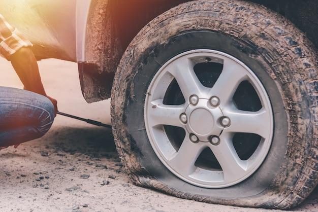 Junger mann ändert reifen auf auto die straße, weil er im hellen sunligh reparierte