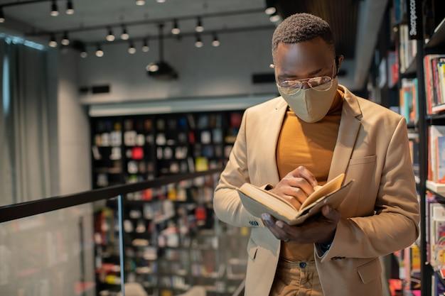 Junger mann afrikanischer abstammung, der ein buch liest
