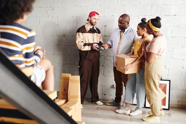 Junger mann afrikanischer abstammung, der mit kreditkarte für hausrenovierungsmaterialien bezahlt