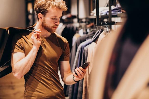 Junger mann am herrenbekleidungsshop sprechend am telefon