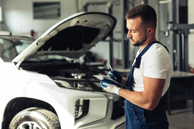 Junger mann am service, der auto repariert