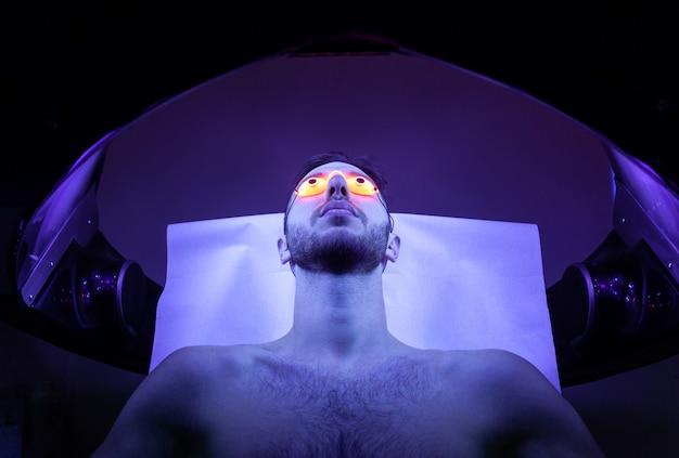 Junger mann am solarium im schönheitssalon.