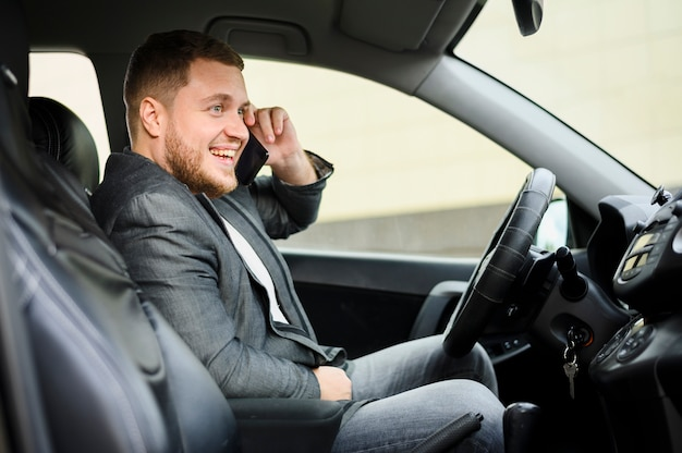 Junger mann am steuer mit seinem telefon am ohr