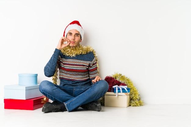 Junger mann am weihnachtstag augen geöffnet halten, um eine erfolgschance zu finden.
