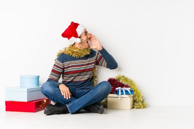 Junger mann am weihnachtstag blinken in die kamera durch die finger, verlegenes bedeckungsgesicht.