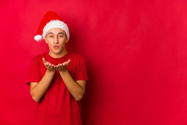 Junger mann am weihnachtstag, der lippen faltet und palmen hält, um luftkuss zu senden.