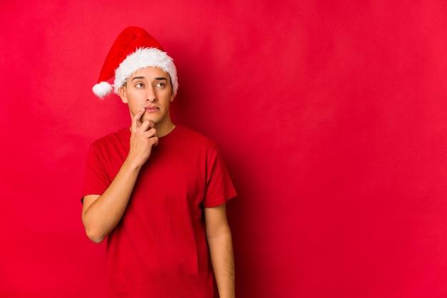 Junger mann am weihnachtstag, der seitlich mit zweifelhaftem und skeptischem ausdruck schaut.