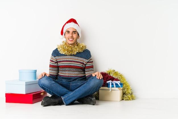 Junger mann am weihnachtstag, der traurig und nachdenklich sich fühlt und kopienraum betrachtet.