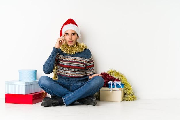 Junger mann am weihnachtstag, der wegen etwas entsetzt ist, das sie gesehen hat.