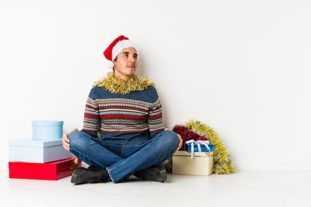 Junger mann am weihnachtstag eine auszeitgeste zeigend.