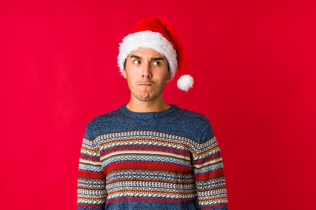 Junger mann am weihnachtstag lächelt und zeigt mit den fingern auf den mund.