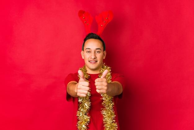 Junger mann am weihnachtstag mit den daumen ups, beifall über etwas, unterstützung und respektkonzept.
