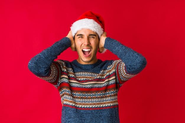 Junger mann am weihnachtstag sorglos und aufgeregt zujubelnd. sieg-konzept.