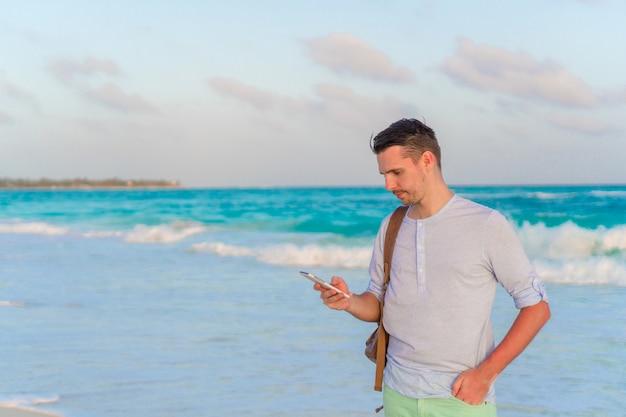 Junger mann am weißen tropischen strand