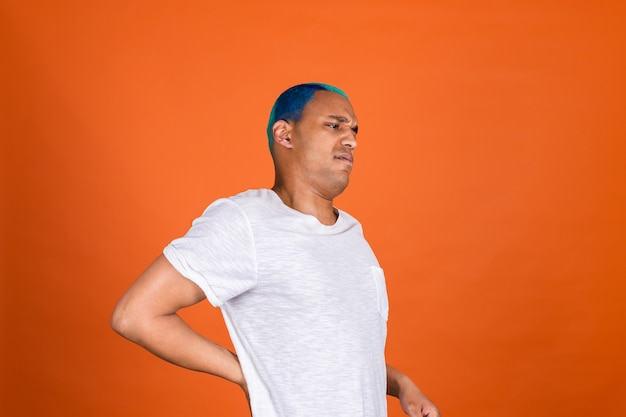 Junger mann an orangefarbener wand, der rückenschmerzen hat und unglücklich leidet
