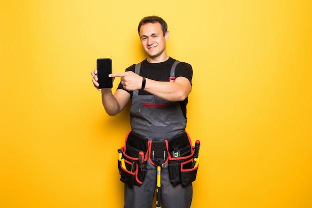 Junger mann arbeiter mit werkzeuggürtel zeigte auf telefon