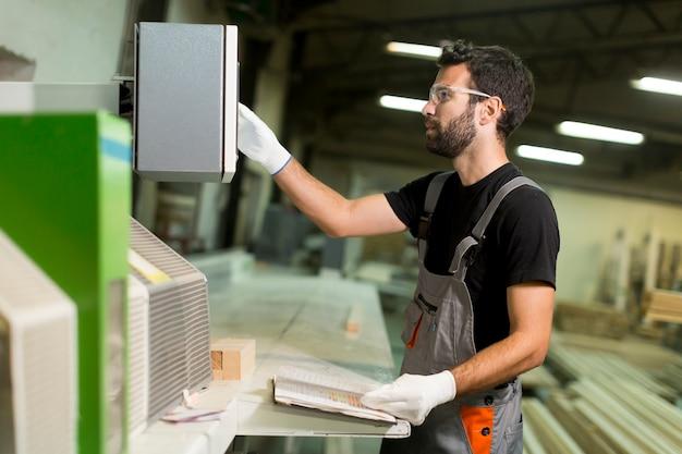 Junger mann arbeitet in einer fabrik für die produktion von möbeln