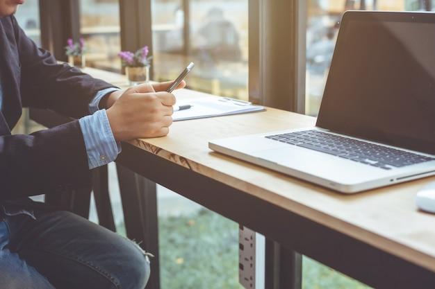 Junger mann arbeitet mit smartphone und notebook.