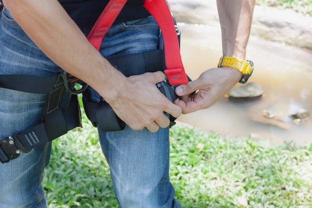 Junger mann asian tragen das sicherheitsgeschirr für arbeit in der höhe.