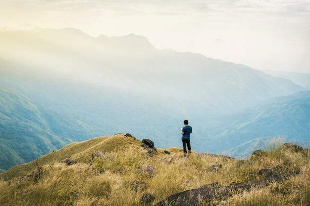 Junger mann asien-tourist des instagram-filters am berg passt über den nebelhaften und nebeligen morgensonnenaufgang auf
