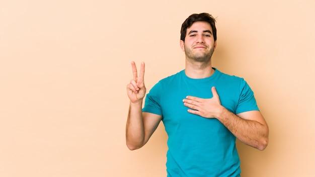 Junger mann auf beige wand, der einen eid leistet und hand auf brust legt.