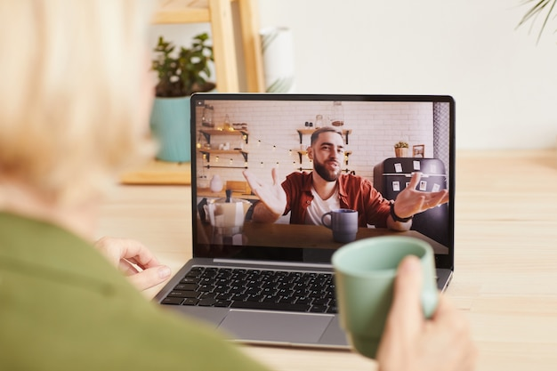 Junger mann auf computermonitor, der online mit frau spricht, die am tisch mit tasse kaffee sitzt