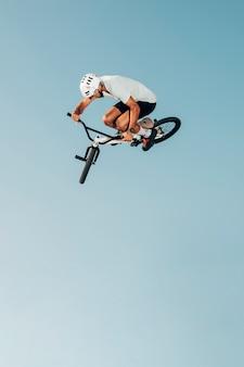 Junger mann auf dem fahrrad, das niedrige winkelsicht springt
