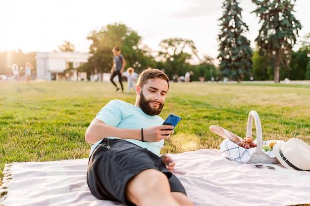 Junger mann auf dem picknick mit dem obstkorb, der den handy simst im park betrachtet