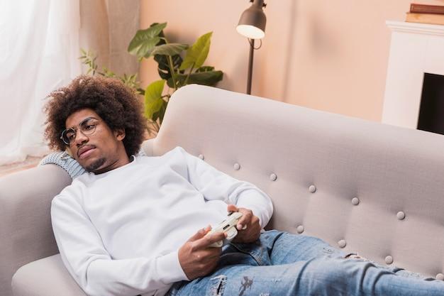 Junger mann auf der couch, die spiele spielt