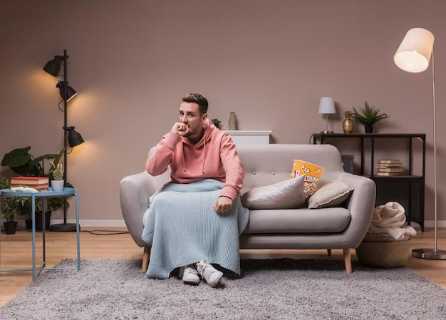 Junger mann auf der couch film genießend