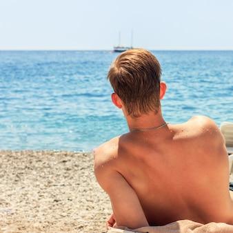 Junger mann auf einem liegestuhl am strand schaut auf das meer