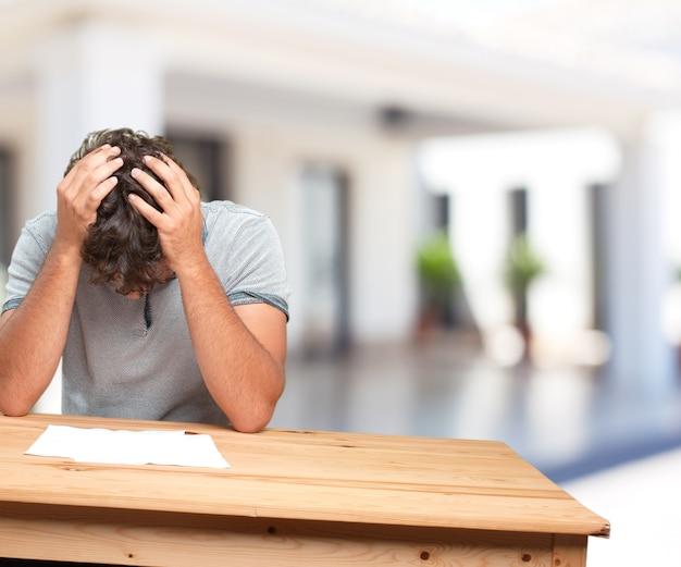 Junger mann auf einem tisch. sorge ausdruck