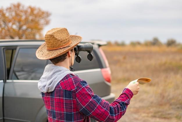 Junger mann auf einer autoreise mit dem auto unter verwendung des fernglases und suchen den weg