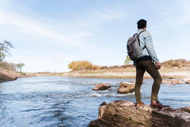 Junger mann auf felsen nahe dem see