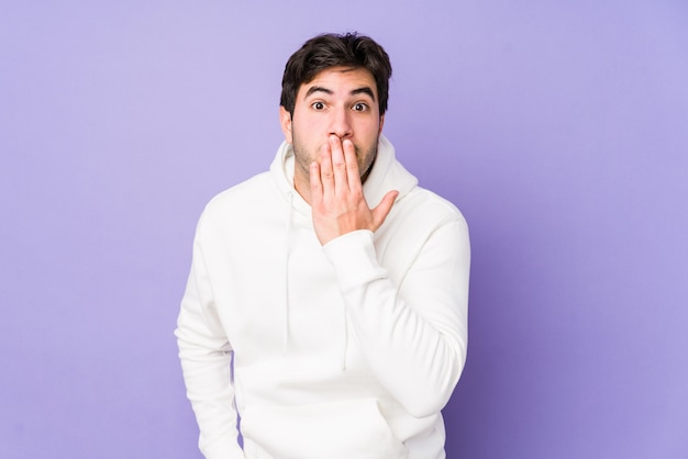 Junger mann auf lila wand schockiert, mund mit der hand bedeckend