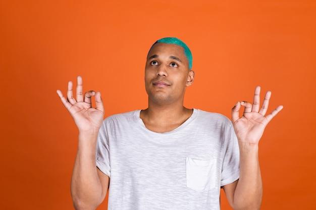 Junger mann auf orangefarbener wand meditiert mit yogageste