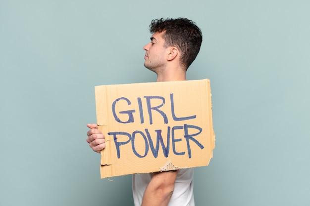 Junger mann auf profilansicht, die plakat mit text hält: frauenpower
