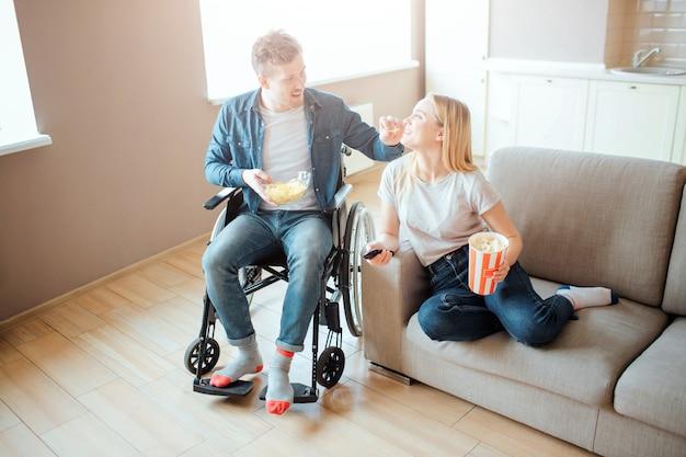 Junger mann auf rollstuhl, der neben frau auf sofa sitzt. person mit behinderung und besonderen bedürfnissen. film schauen. mit chips und popcorndose bown halten.