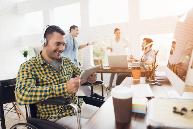 Junger mann auf rollstuhl mit kopfhörern im büro.
