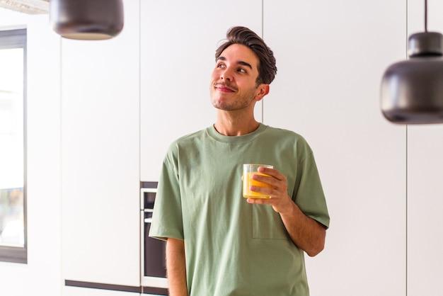 Junger mann aus gemischten rassen, der in seiner küche orangensaft trinkt und davon träumt, ziele und zwecke zu erreichen