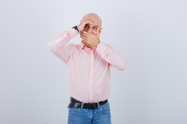 Junger mann bedeckt den mund mit der hand