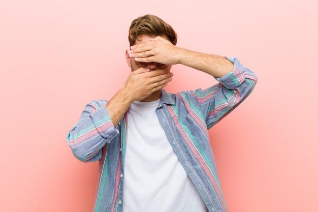 Junger mann bedeckt gesicht mit beiden händen und sagt nein zur kamera! bilder ablehnen oder fotos vor rosa hintergrund verbieten