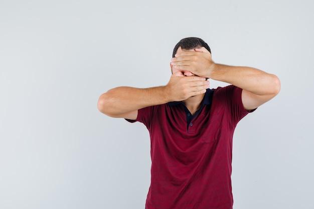 Junger mann bedeckt gesicht mit seinen händen im roten t-shirt und schaut ängstlich, vorderansicht.