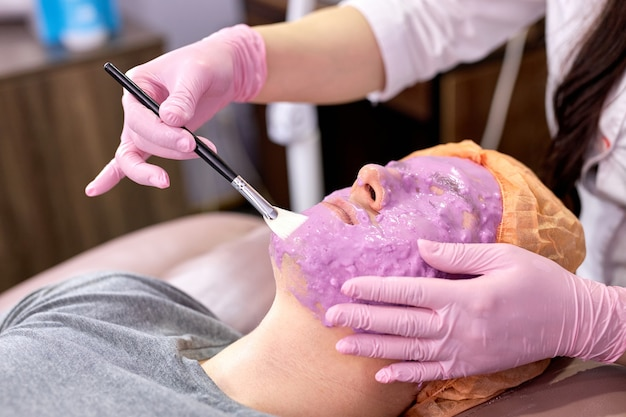 Junger mann bei kosmetologischen eingriffen im schönheitssalon bei der professionellen kosmetikerin. hautpflege, schönheitskonzept.