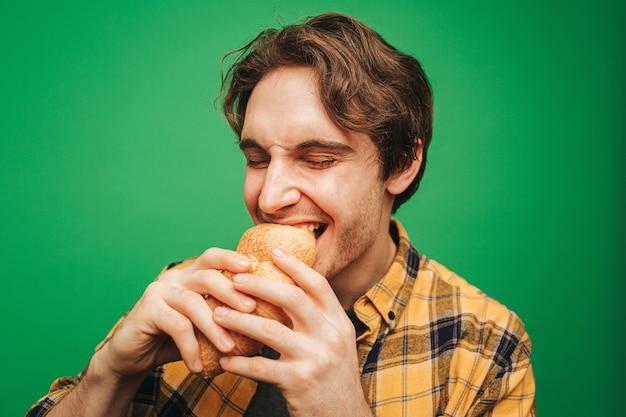 Junger mann beißt croissant